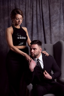 A handsome young man in a suit sits in a chair and holds the hand of a beautiful woman in a black evening dress
