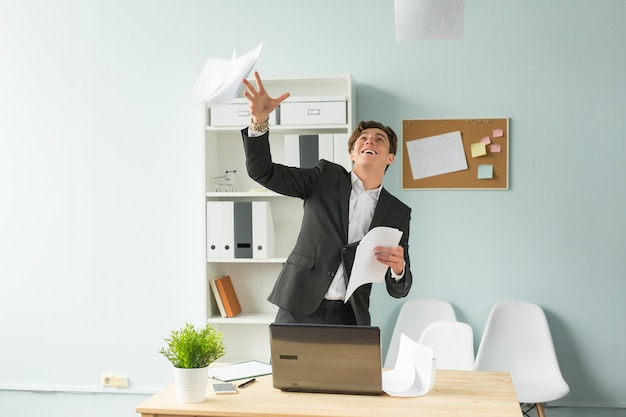 Handsome and young man in suit throws up sheets of paper in office
