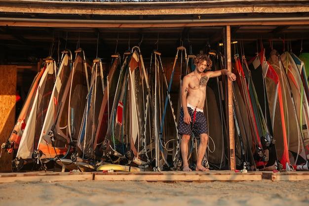 Красивый молодой человек-серфер, стоящий возле пункта снаряжения для виндсерфинга на пляже