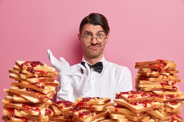 Красивый молодой человек в окружении бутербродов с арахисовым маслом