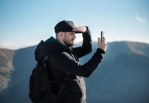 Красивый молодой человек берет на смартфон горный пейзаж. каспровы верх. польша.