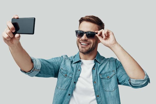スマートフォンを使用してselfieを取り、灰色の背景に立って笑っているハンサムな若い男