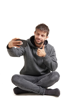 Handsome young man taking a selfie with his cellphone while liking it, isolated on white. he wears gray clothes.