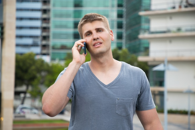 Handsome young man talking by smartphone