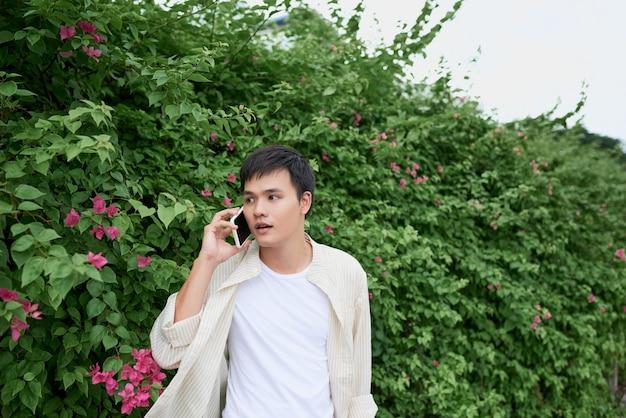 Красивый молодой человек разговаривает по телефону во время прогулки по улице