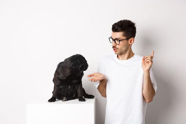 犬のコマンドを教えて、かわいい黒いパグと話し、白の上に立っているハンサムな若い男