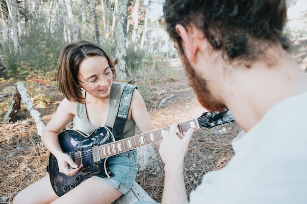 Красивый молодой человек обучает хипстерскую девушку играть на гитаре в парке. изучение и преподавание концепций, хобби, лес и природа, свободное время