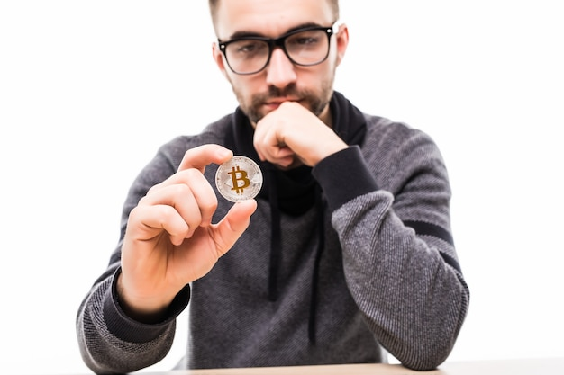 Handsome young man thinking over bitcoin isolated on white