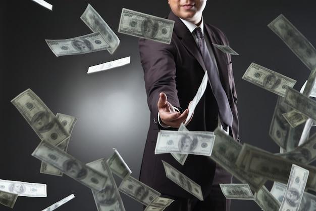 お金を投げるハンサムな若い男