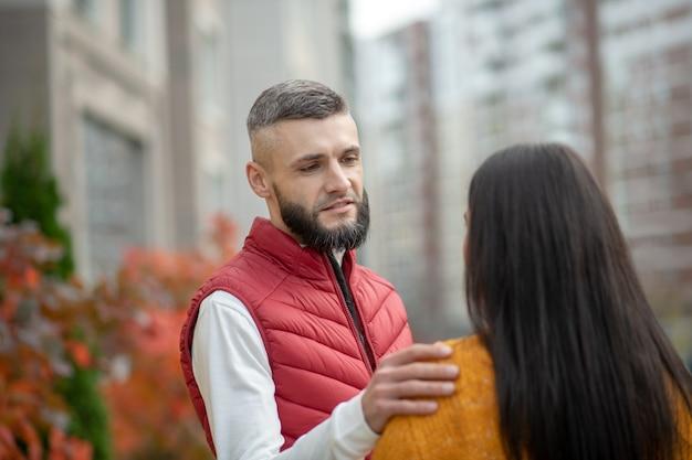 Красивый молодой человек трогает плечо своей подруги, рассказывая ей о своих чувствах