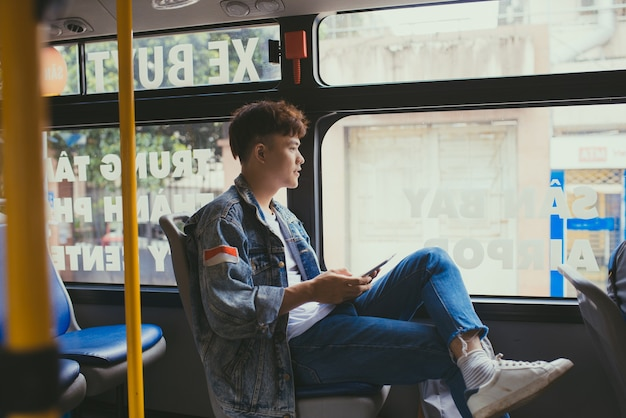 버스로 여행하고 디지털 태블릿을 사용하는 잘생긴 청년