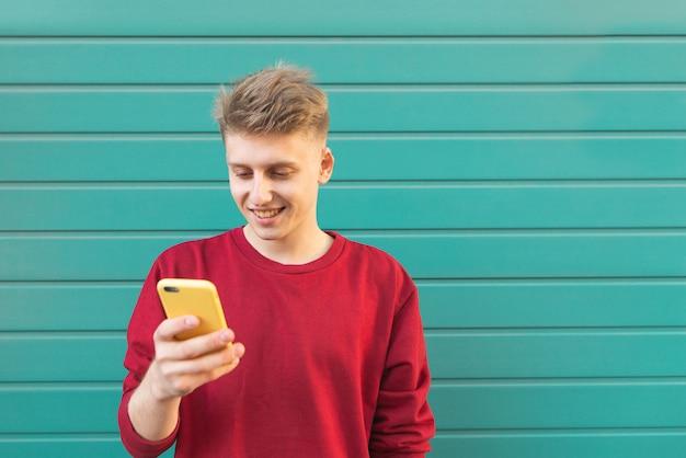 잘 생긴 젊은 남자는 스마트 폰을 사용 하여 화면을보고 청록색 벽에 웃 고.