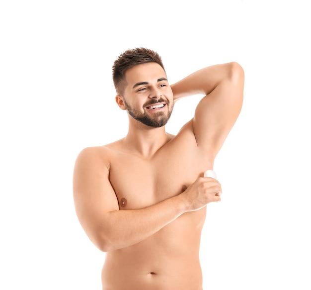 Красивый молодой человек с помощью дезодоранта на белой поверхности