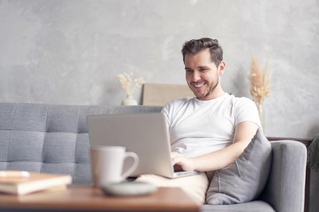 Красивый молодой человек, используя свой ноутбук с улыбкой, сидя на диване у себя дома.