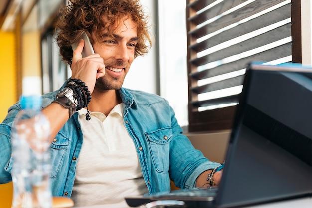 레스토랑 바에서 점심을 먹는 동안 노트북을 사용하는 잘 생긴 젊은 남자.