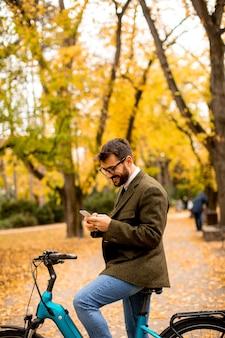 秋の公園で電動自転車で携帯電話を使用してハンサムな若い男
