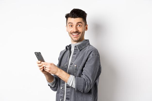 스마트 폰을 사용 하 고 카메라를보고 잘 생긴 젊은 남자. 백인 남자는 흰색 바탕에 서 행복 한 얼굴로 전화 채팅.