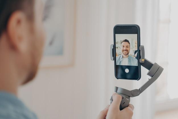 Красивый молодой человек ведет видеоблог или записывает видео на смартфон с большим портативным стабилизатором карданного подвеса, стоя в гостиной дома на заднем плане. концепция видеоблогов и видеоблогов