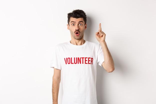 Bel giovane in maglietta volontaria che ha un'idea, alzando il dito e dicendo suggerimento, puntando verso l'alto, in piedi su sfondo bianco.