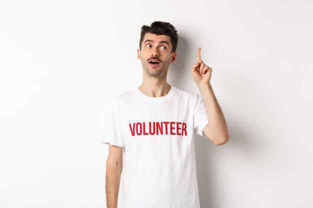 Bel giovane in maglietta volontaria che ha un'idea, alzando il dito e dicendo suggerimento, sfondo bianco.
