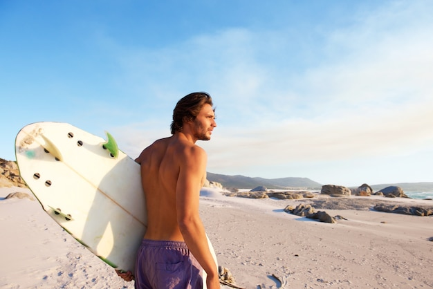Handsome young man walking on beach with surfboard