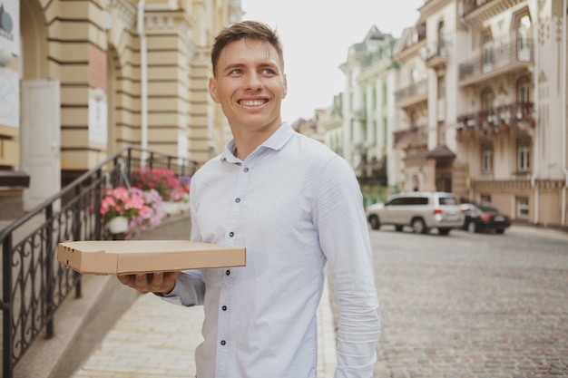 Handsome young man walking on city street with pizza box
