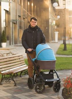 路上でベビーカーで赤ちゃんと一緒に歩くハンサムな若い男