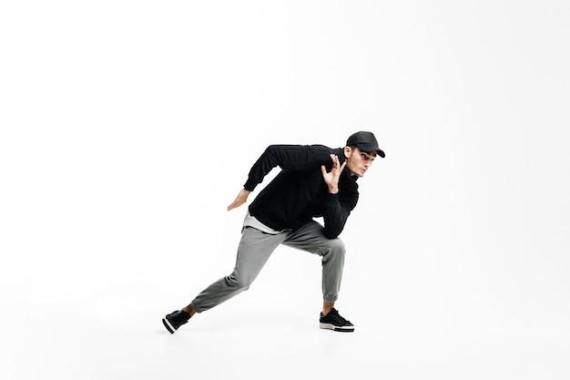 黒のスウェットシャツ、灰色のズボン、白い背景の上でストリートダンスを踊る帽子を身に着けているハンサムな若い男