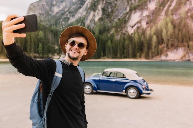 イタリアの山の湖の前に立っている自分の写真を撮る茶色の帽子とサングラスを身に着けているハンサムな若い男