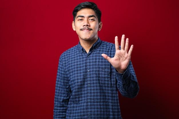 Красивый молодой человек в повседневной одежде показывает и показывает пальцами номер пять, уверенно и счастливо улыбаясь на красном фоне