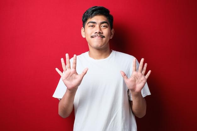 赤い背景の上に自信を持って幸せに笑っている間、指番号10を表示し、上向きにカジュアルな服を着ているハンサムな若い男