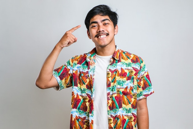 カジュアルなシャツを着て笑顔のハンサムな若い男が両手指で頭を指して、素晴らしいアイデアや考え、白い背景の上の良い思い出