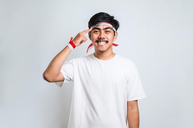 캐주얼 셔츠를 입은 잘생긴 청년은 양손 손가락으로 머리를 가리키며 웃고, 훌륭한 아이디어나 생각, 흰색 배경에 대한 좋은 기억