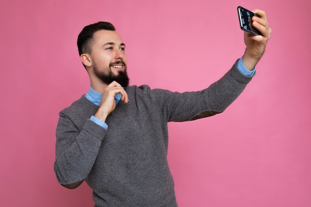 Handsome young man wearing casual stylish clothes standing isolated over background wall holding smartphone taking selfie photo looking at mobile phone screen display