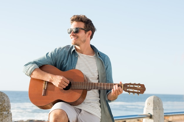 Handsome young man wearing sunglasses and playing guitar on fence near beach