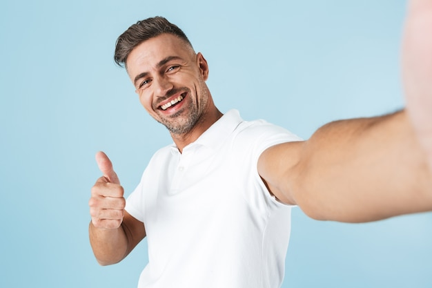 Handsome young man wearing white t-shirt standing over blue, taking a selfie, giving thumbs up