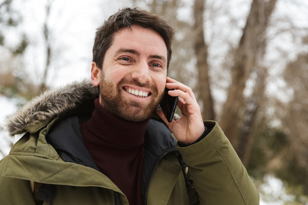 Handsome young man wearing winter jacket standing outdoors, talking on mobile phone