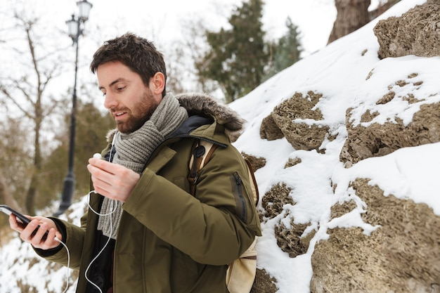 Handsome young man wearing winter jacket using mobile phone while walking outdoors, listening to music with earphones