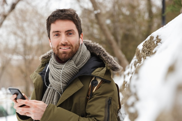 야외에서 걷는 동안 휴대 전화를 사용하여 겨울 재킷을 입고 잘 생긴 젊은 남자, 이어폰으로 음악을 듣고