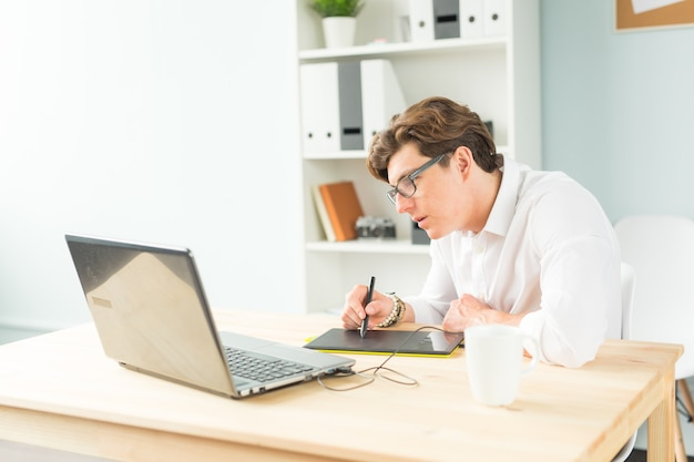 Handsome young man in white shirt using graphic tablet at wooden table