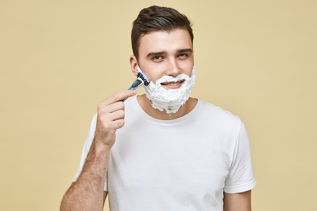 Handsome young man in white t-shirt holding razor while shaving beard against grain to avoid skin irritation with smile, taking care of his appearance. masculinity, style and beauty