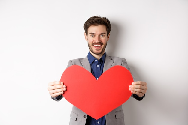幸せなバレンタインデーを願って、大きな赤いハートのサインを与えて、笑顔のハンサムな若い男は、白い背景の上にスーツに立って、恋人に驚きます。