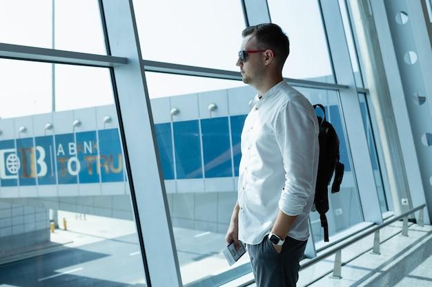 Красивый молодой человек с рюкзаком в аэропорту