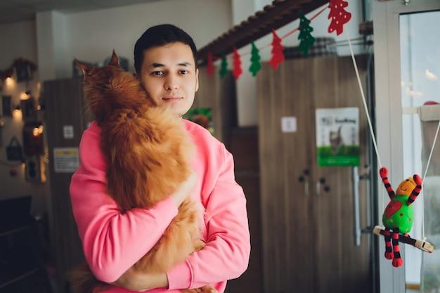 赤毛のメインクーン猫を抱き締めるひげを持つハンサムな若い男。子猫を手に持った白いtシャツの男動物愛好家。