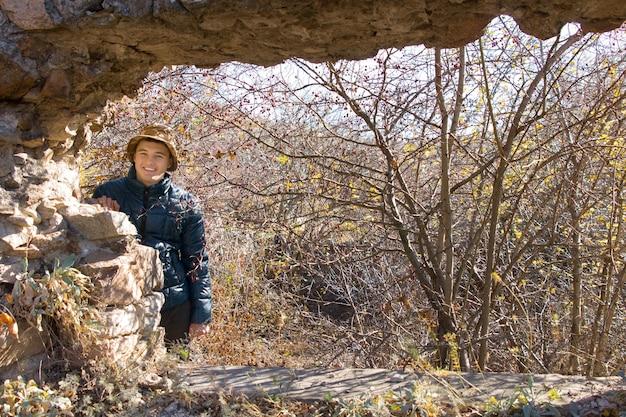 葉のない秋の木々を背景に古い廃墟の石造りの建物を見て立っている陽気なフレンドリーな笑顔を持つハンサムな若い男