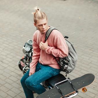 Красивый молодой человек с прической в розовом свитере с рюкзаком и скейтбордом сидит на мотоцикле