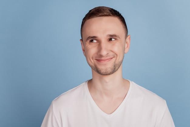 Красивый молодой человек с счастливым лицом, счастливая позитивная улыбка, мечта, думать, смотреть пустое пространство, изолированное на синем цветном фоне