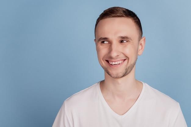 Красивый молодой человек со счастливым лицом, стоящий с уверенной улыбкой, смотрит пустое пространство, изолированное на синем цветном фоне
