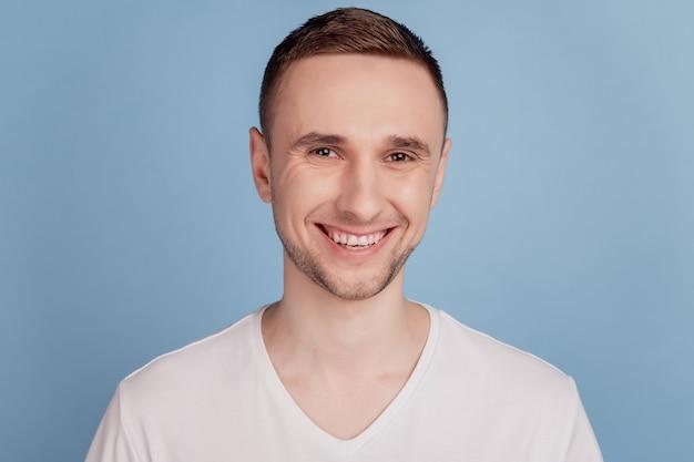 Красивый молодой человек со счастливым лицом, стоящий с уверенной улыбкой, показывает зубы, изолированные на синем цветном фоне