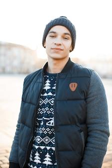 ファッショナブルなジャケットのクリスマスニットセーターでヴィンテージのスタイリッシュな帽子に甘い笑顔でハンサムな若い男が街に立っています。散歩のためのスタイリッシュな幸せな魅力的な男。